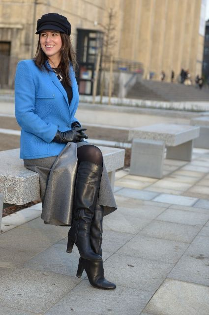 With black cap, blue blazer, gray midi skirt and black high boots