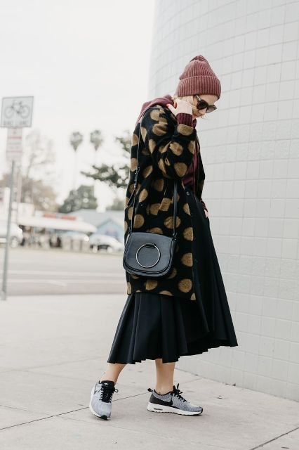 With black pleated midi skirt, hat, black bag and black and gray sneakers