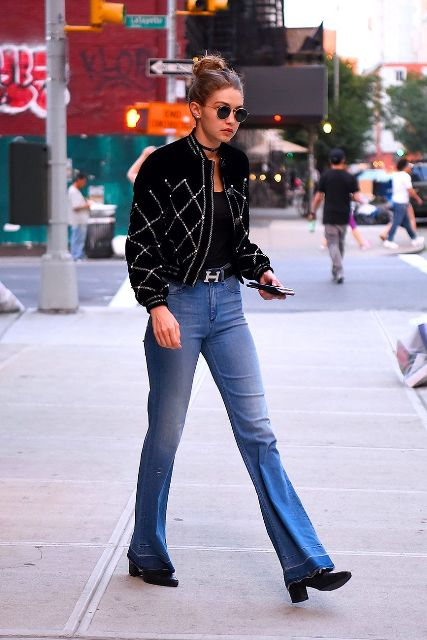 With black top, embellished jacket, rounded sunglasses and black low heeled shoes