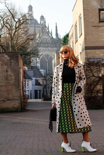 With black turtleneck, printed midi skirt, black bag and white and green boots