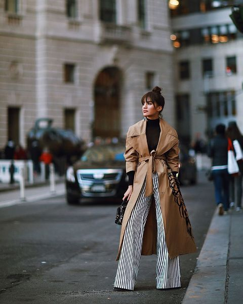 With black turtleneck, white and black striped wide leg pants and bag