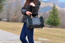 With black wide brim hat, black puffer jacket, leather and suede bag and jeans