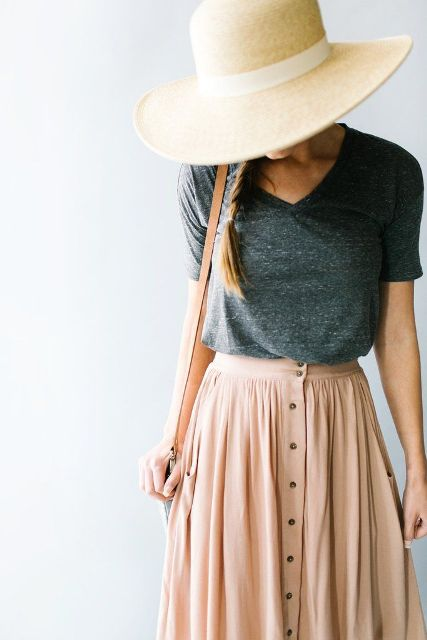 With dark gray t shirt, brown bag and wide brim hat