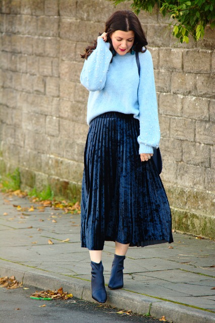 With light blue loose sweater, bag and navy blue boots