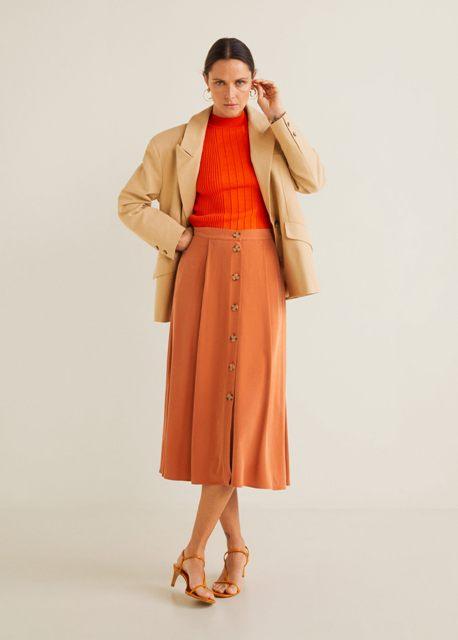 With orange shirt, beige blazer and orange high heels