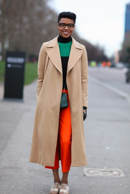 With red cropped pants, green bag, lace up flat shoes and green and black sweater