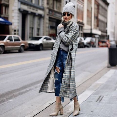 With super distressed jeans, beige ankle boots, gray sweater and hat