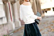 With white one shoulder sweater and clutch