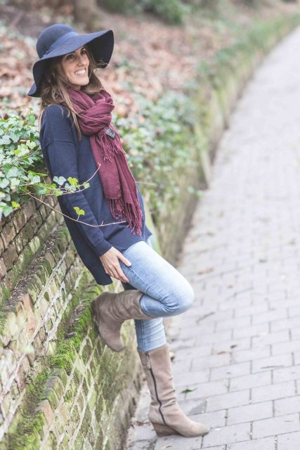 With wide brim hat, light blue jeans, purple scarf and navy blue sweatshirt