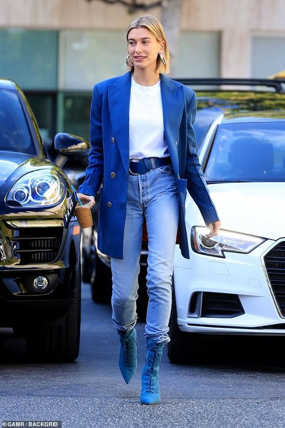 a Hailey Baldwin rocking a bold look with a white tee, blue jeans, blue lace up booties and an oversized jacket
