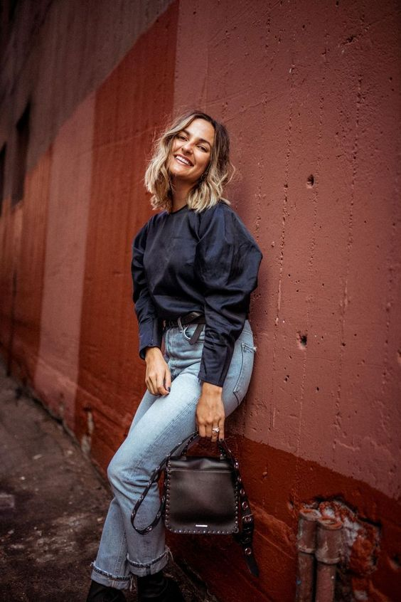 a black puffy sleeve blouse with a high neckline, bleached blue jeans, black booties and a black bag