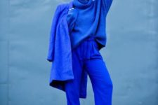 a bold classic blue monochrome outfit with an oversized sweater, pants, a coat and white boots