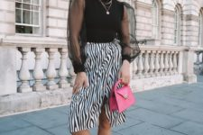 a bold outfit wiht a black top with sheer puffy sleeves and a zebra print wrap skirt, white sneakers and a pink bag
