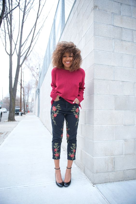 a bright outfit with a fuchsia long sleeve top, black embroidered jeans and black ankle strap shoes