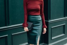 a burgundy top with long sleeves, a green pencil midi skirt, black shoes and a black clutch