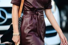 a burgundy wrap midi dress with short sleeves and a printed bag plus layered necklaces for a chic look