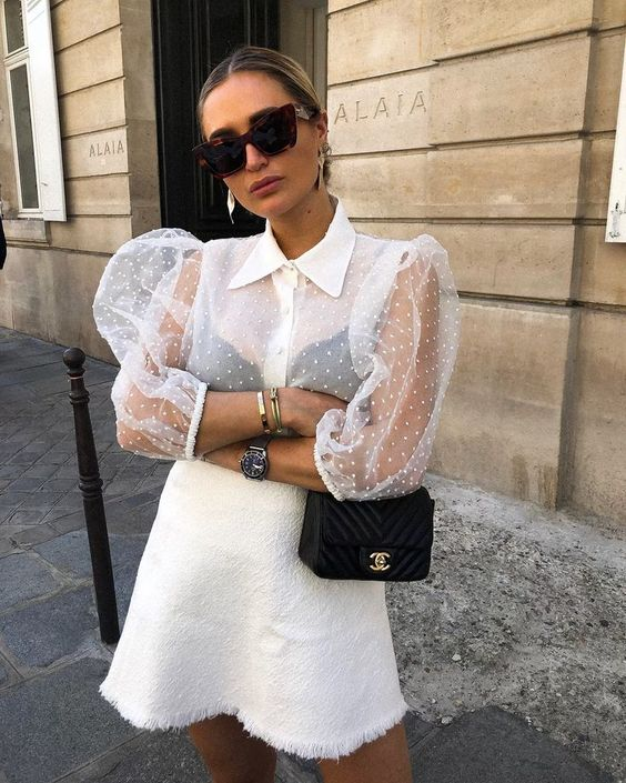 a chic white polak dot blouse with sheer puffy sleeves and a white lace mini skirt with fringe plus a black bag