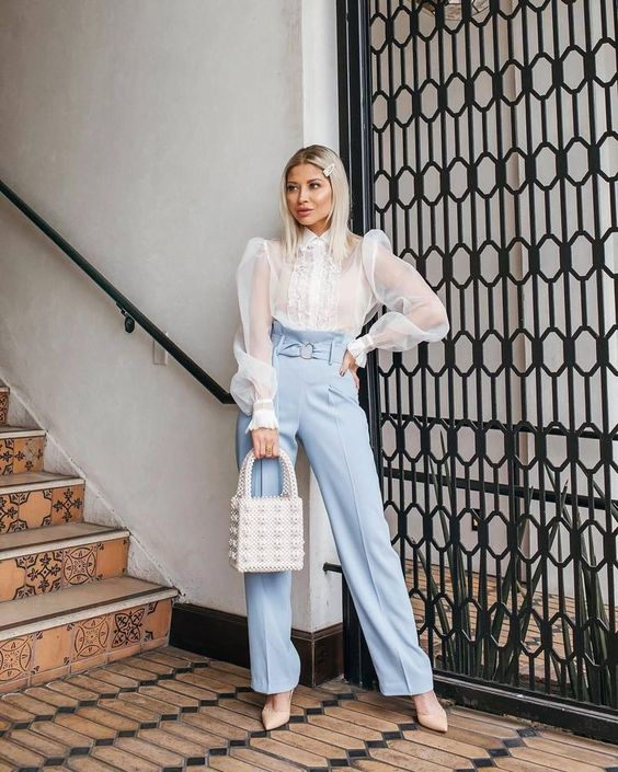 a chic work outfit with light blue high waisted pants and a white sheer puffy sleeve blouse, nude shoes and an embellished bag