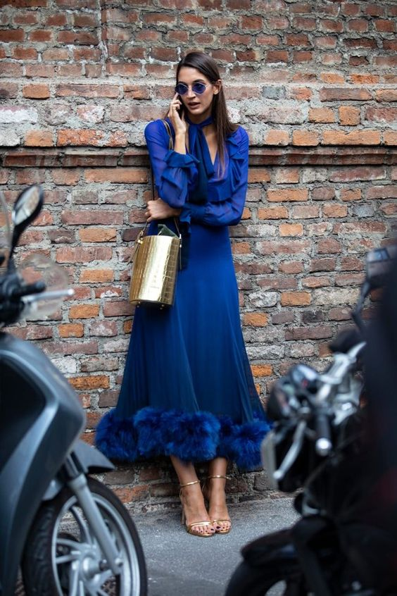 a classic blue midi A line dress with ruffled sleeves and a feather skirt, silver shoes and a gold clutch
