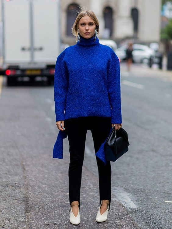 a classic blue oversized sweater, black jeans, white shoes, a black bag and statement earrings