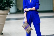 a classic blue pantsuit, silver shoes and a printed clutch for a bold work look is a chic idea