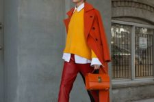 a colorful look with red leather pants, a marigold sweater, a red coat and bag plus strappy heels