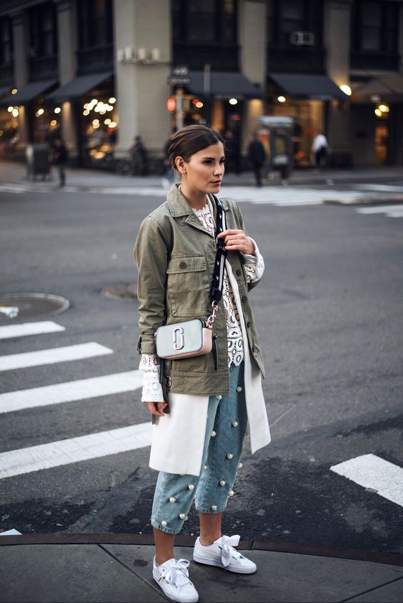 a crochet top, large pearl jeans, white sneakers, an olive green jacket and a neutral bag