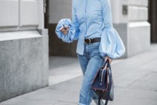 a daring look with a blue puffy sleeve blouse in Victorian style, blue jeans, black shoes and a navy bag