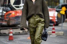 a dark green oversized sweater, light green leather pants, a navy bag and amber booties