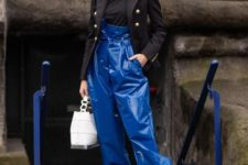 a fashion-forward look with a black top, a blazer, classic blue leather pants, booties and a white bag
