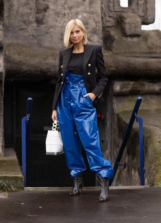 a fashion forward look with a black top, a blazer, classic blue leather pants, booties and a white bag