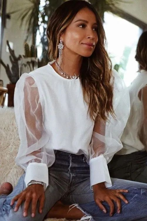 a fashionable look with a white top with sheer puffy sleeves, blue fringed jeans and statement celestial accessories