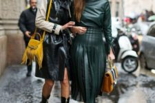 a forest green top and a pleated midi A-line skirt, black booties and a brown leather bag