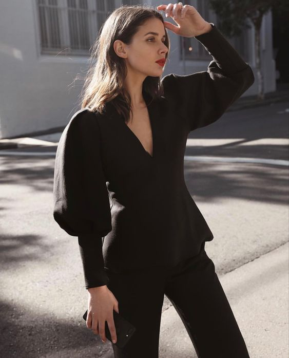 a gorgeous black pantsuit with a blazer with puffy sleeves and a deeo V-neckline plus a clutch for a special occasion