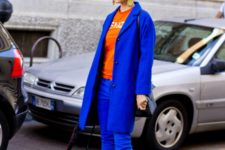 a red tee, classic blue pants, a coat, orange shoes for a bold and super-contrasting look