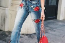 a sexy look with a white one shoulder top, blue jeans with red floral embroidery, black heels and a red bag