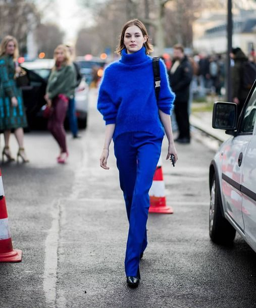 a statement classic blue outfit with an oversized sweater, pants, black booties and a comfy bag