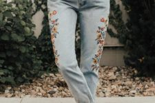 a stylish look with a white sweater, whitewashed jeans with floral embroidery and brown booties