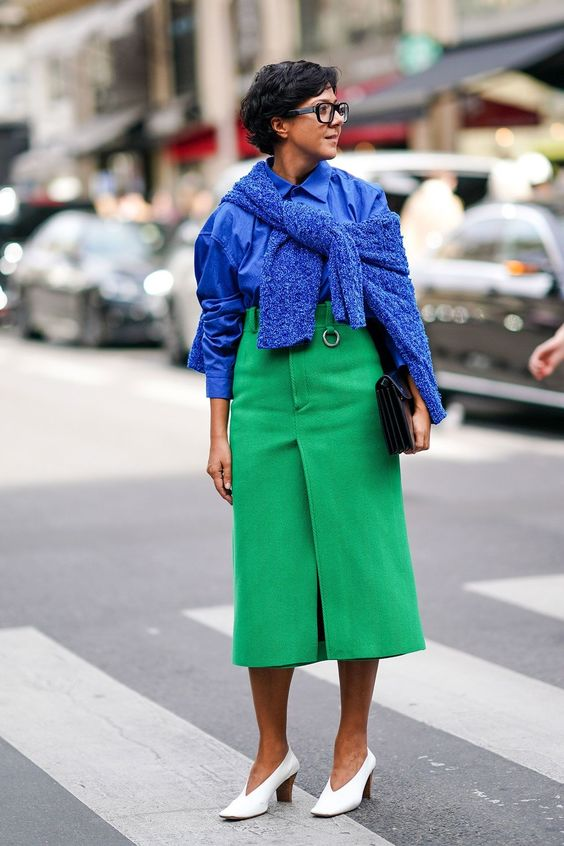 a trendy colorful outfit with a classic blue shirt, sweater, a bold green midi skirt, white shoes and a clutch