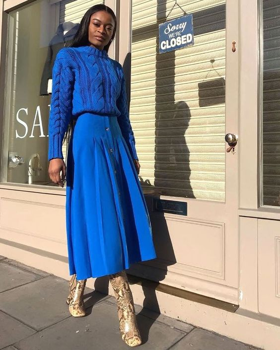 a trendy look in classic blue with a braided sweater, a plaid skirt on buttons and snake print boots