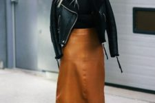 a trendy winter look with a black turtleneck, an amber midi skirt, matching boots and a black shearling coat
