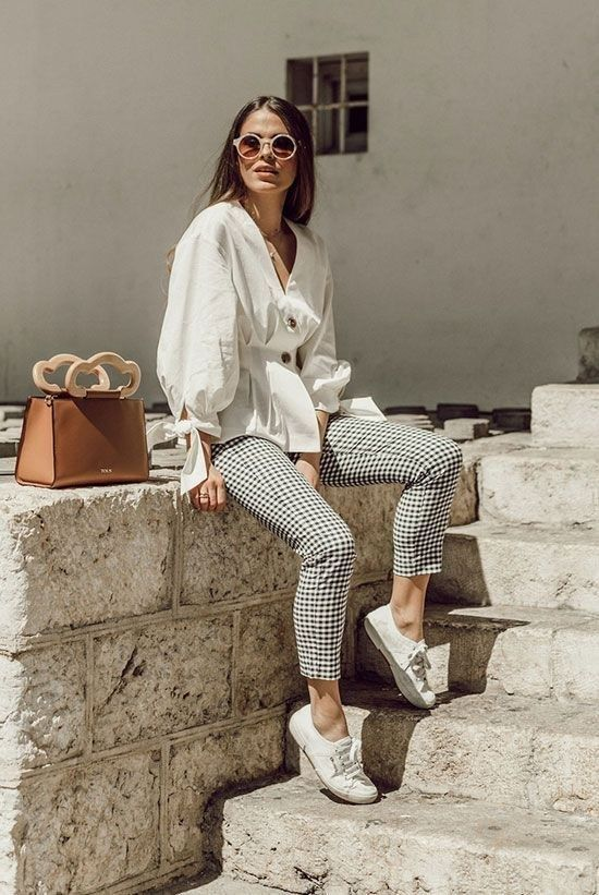 a vacation outfit with a white puffy sleeve blouse on buttons, checked pants, white sneakers and a brown bag