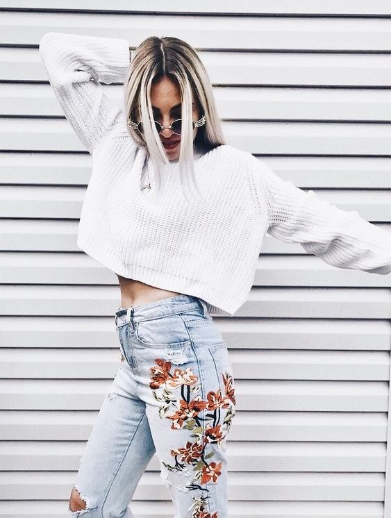a white oversized chunky knit crop sweater paired with whitewashed embroidered jeans for a bold look
