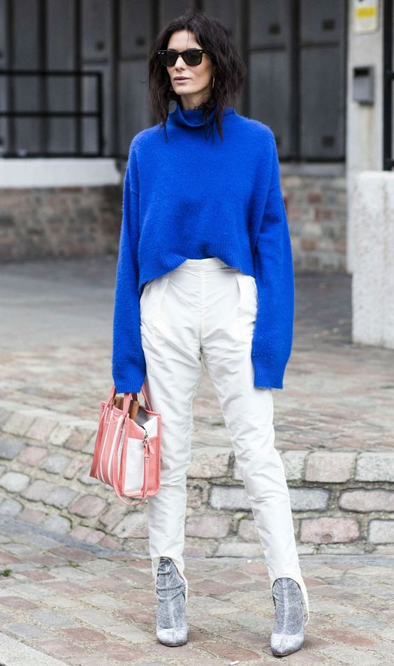 an oversized classic blue sweater, white pants, grey suede booties and a striped bag