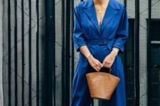 an oversized classic blue umpsuit with a plunging neckline, printed shoes and a brown leather bag