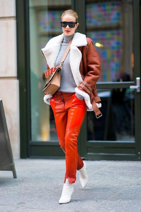 orange leather pants, white booties, a grey sweater, a brown shearling coat and brown bag