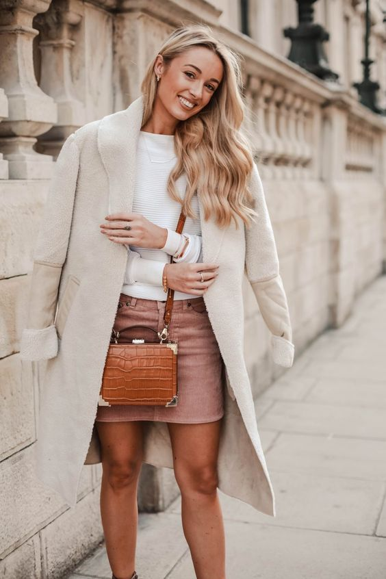 a white sweater, a pink corduroy skirt, a white shearling coat and an amber crossbody bag