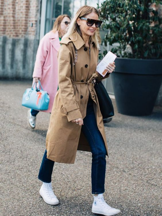straight navy jeans, white high tops, a camel trench and a large bag for a spring outfit