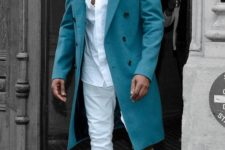 03 Kanye West wearing a white shirt, white jeans, tan sneakers and a turquoise coat
