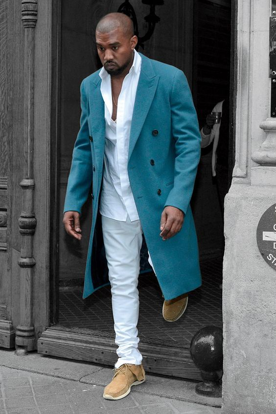Kanye West wearing a white shirt, white jeans, tan sneakers and a turquoise coat